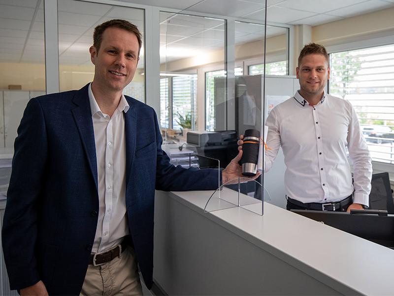 Geschäftsführer Christian Frede (links) überreicht den Coffee to go-Becher an Domenic Lingner, stellvertretend für die 330 Mitarbeitenden